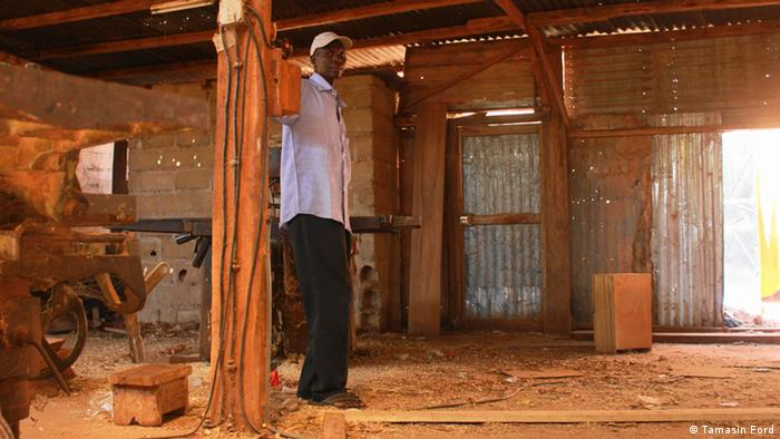 Sinayoko stands in his carpenter's workshop off the main road in central Bamako
