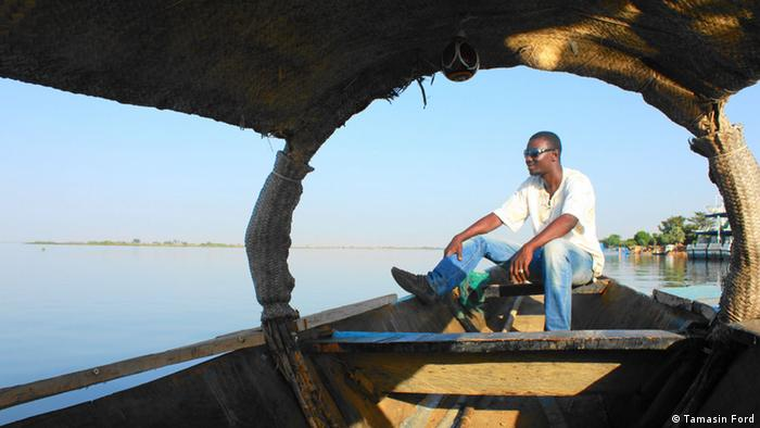 Balo sits on his pinasse, a river boat used for taking tourists down the Niger River.