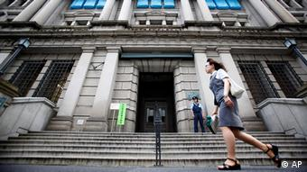 A woman walks by the Bank of Japan building in Tokyo. Japan's central bank kept its benchmark interest rate unchanged Tuesday, Aug. 10, 2010, acknowledging worries about falling prices and other risks to the nation's still fragile economic recovery.
