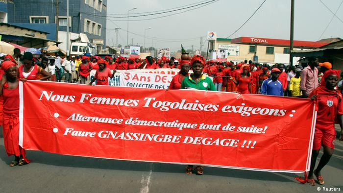 Women dressed in red carry a banner as they march during a protest against Togo's government in the capital Lome, December 20, 2012. The banner reads, We, Togolese women, demand: Democratic alternation immediately! - Faure Gnassingbe, step down!. REUTERS/Noel Kokou Tadegnon (TOGO - Tags: POLITICS CIVIL UNREST)
