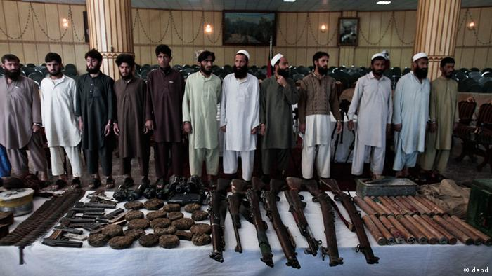 A long line of Afghan men stand behind a table, which has their weaponry on it. (Photo:Rahmat Gul/AP/dapd)