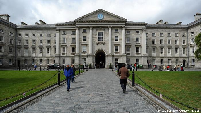 People stand in front of Trinity College Dublin.