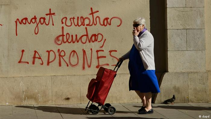 A women walks past graffiti reading Pay your debts thieves in Barcelona during the Spanish debt crisis 2012.