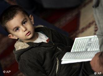 A boy listens to a verse from the Koran
