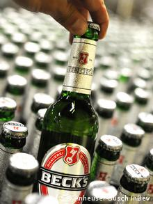 Hand lifting green Becks bottle from production array