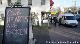 A sign in the Sandy Hook village of Newtown, Connecticut reads, Our hearts are broken
