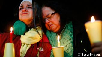 Donna Soto (R), mother of Victoria Soto, the first-grade teacher at Sandy Hook Elementary School who was shot and killed while protecting her students, hugs her daughter Karly while mourning their loss at a candlelight vigil in honor of Victoria at Stratford High School on December 15, 2012 in Stratford, Connecticut. Twenty-six people were shot dead, including twenty children, after a gunman identified as Adam Lanza opened fire in the school. Lanza also reportedly had committed suicide at the scene. A 28th person, believed to be Nancy Lanza was found dead in a house in town, was also believed to have been shot by Adam Lanza. (Photo by Jared Wickerham/Getty Images)