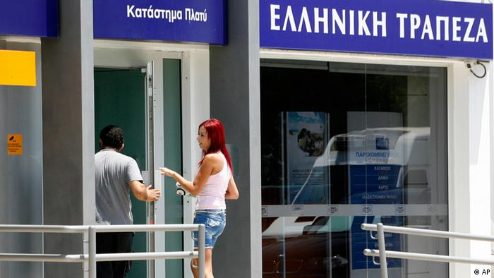 People entering in a branch of Hellenic Bank in central Nicosia , Cyprus, Thursday, June 28, 2012. Cyprus became the fifth eurozone country this week to ask for a bailout from its partners in the currency union in order to prop up its Greece-exposed banks and flagging economy. Officials from the European Commission, the European Central Bank and the International Monetary Fund will begin assessing next week how much bailout money Cyprus will need. (Foto:Philippos Christou/AP/dapd)