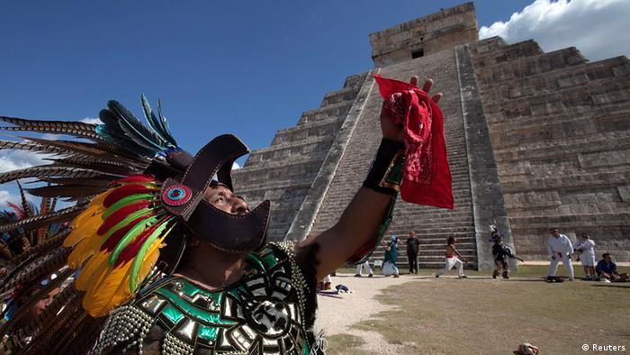 Homem em trajes típicos dos astecas diante da pirâmide de Kukulkan, no México