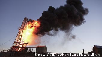 An oil rig burns bright orange against a dark sky with black smoke (Photo: Mary Evans Picture Library)