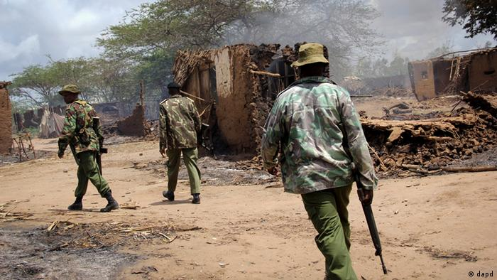 Kenyan police patrol past smoldering houses that had been burned in the village of Nduru, following renewed clashes between farmers and herders in the Tana River delta area of southeastern Kenya, Tuesday, Sept. 11, 2012.