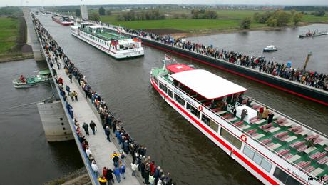 A boat using the Magdeburg Water Bridge while crowds of people watch from the railings.