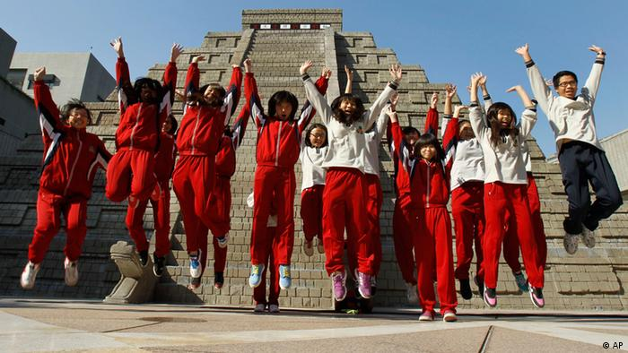 Students jump together to pose for photographers in front of a mock pyramid after the countdown time when many believe the Mayan people predicted the end of the world, Friday, Dec. 21, 2012, in Taichung, southern Taiwan. (Foto:Wally Santana/AP/dapd)
