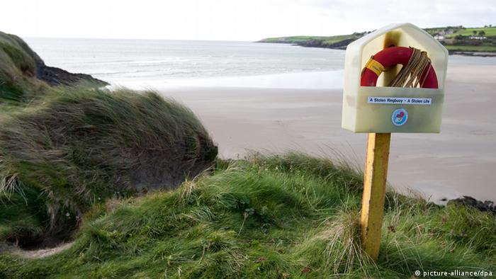 Ein Rettungsring in einem Plastikbehälter mit der Aufschrift 'A Stolen Ringbuoy - A Stolen Life' (Ein gestohlener Rettungsring - Ein gestohlenes Leben) (Foto: dpa)