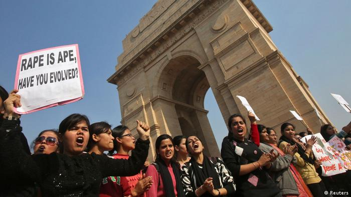 Demonstrators hold placards in front of the India Gate as they take part in a protest rally organised by various women's organisations in New Delhi December 21, 2012. Thousands of protesters took to the streets in various parts of the country to demand urgent action against the men who took turns to rape a 23-year-old woman on a moving bus on December 16, local media reports said. REUTERS/Adnan Abidi (INDIA - Tags: CRIME LAW CIVIL UNREST)