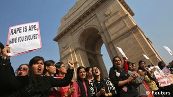 Demonstrators hold placards in front of the India Gate as