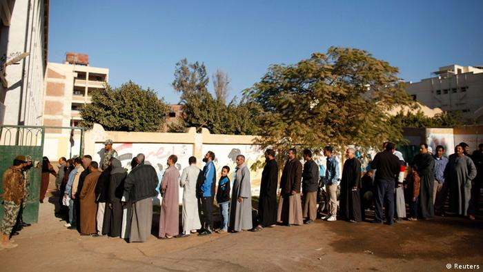 People to wait in line outiside a polling station in Giza, south of Cairo