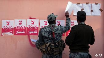 Egyptian military officers hang the list of voters names next to stickers with Arabic writing that reads No for the 2012 constitution on a wall of a polling station during the second round of a referendum on a disputed constitution drafted by Islamist supporters of President Mohammed Morsi in Fayoum, about 100 kilometers ( 62 miles ) south of Cairo, Egypt, Saturday, Dec. 22, 2012.(Foto:Khalil Hamra/AP/dapd)
