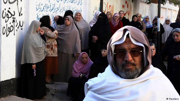 Ein Mann und viel verschleierte Frauen vor einem Wahllokal (Foto: Reuters) Women queue near graffiti (L) which reads Avoid the Brotherhood outside a polling centre to vote during the final stage of a referendum on Egypt's new constitution in Bani Sweif, about 115 km (71 miles) south of Cairo December 22, 2012. Egyptians voted on a constitution drafted by Islamists on Saturday in a second round of balloting expected to approve the charter that opponents say will create deeper turmoil in Egypt. REUTERS/Stringer (EGYPT - Tags: POLITICS ELECTIONS TPX IMAGES OF THE DAY)
