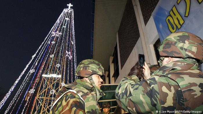 South Korean soldiers stand guard as Christians stage a lighting ceremony in front of a Christmas tree atop a military-controlled hill near the tense land border in Gimpo, west of Seoul, on December 21, 2010. South Korean marines were on guard on December 21, to protect a Christmas tree, the latest focus of tensions with North Korea following Seoul's artillery drill near the disputed sea border a day earlier. AFP PHOTO / KIM JAE-MYUNG (Photo credit should read KIM JAE-MYUNG/AFP/Getty Images)