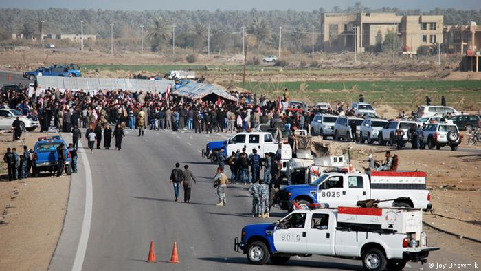 Iraqi protesters, demanding the ouster of premier Nuri al-Maliki, block on December 23, 2012 a highway in western Iraq leading to Syria and Jordan, in Ramadi. The protesters, including local officials, religious and tribal leaders, turned out in Ramadi, the capital of Sunni province of Anbar, to demonstrate against the arrest of nine guards of Finance Minister Rafa al-Essawi. The poster shows former Iraqi vice president Tariq al-Hashemi. AFP PHOTO/STR (Photo credit should read STR/AFP/Getty Images)