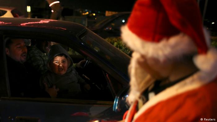 A Palestinian boy reacts to a man dressed as Santa Claus in the West Bank town of Bethlehem ahead of Christmas December 23, 2012. REUTERS/Ammar Awad (WEST BANK - Tags: RELIGION)