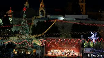 Musicians perform on stage in Manger Square, outside the Church of the Nativity, the site revered as the birthplace of Jesus, on Christmas eve in the West Bank town of Bethlehem December 24, 2012. REUTERS/Ammar Awad (WEST BANK - Tags: RELIGION)