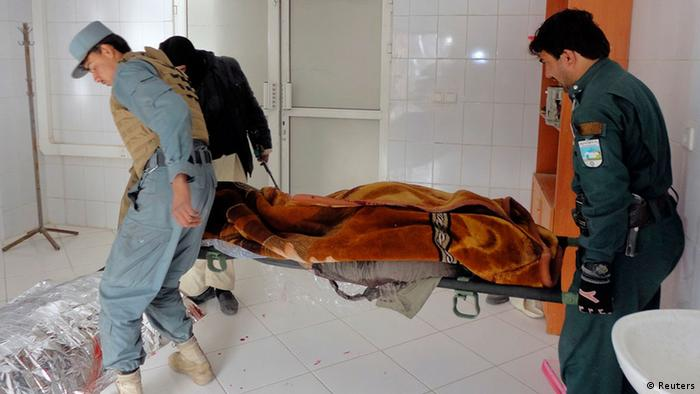 Afghan policemen carry the dead body of a victim at a local hospital after a suicide bomb attack in Khost province December 26, 2012. A suicide bomber killed three people in an attack on a U.S. base in Afghanistan on Wednesday, the same base that is believed to be used by the CIA and which a suicide bomber attacked three years ago killing seven CIA employees. REUTERS/Anwarullah (AFGHANISTAN - Tags: CIVIL UNREST)
