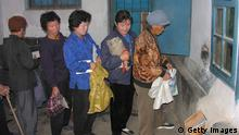 SOHUNG COUNTY, NORTH KOREA, OCTOBER 17: North Korean women queue to receive corn at a public distribution centre on October 17, 2005 in Sohung County, north Hwanghae province, North Korea. According to the WFP website North Korea has a 'lack of agricultural inputs such as fertilisers' and a 'limited capacity to access international capital markets and import food'. (Photo by Gerald Bourke/WFP via Getty Images)