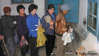 North Korean women queue to receive corn at a public distribution centre on October 17, 2005 in Sohung County, north Hwanghae province, North Korea (Photo: Gerald Bourke/WFP via Getty Images)