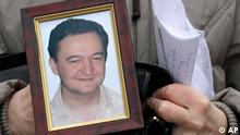 Hands holding a photo of Sergei Magnitsky (AP)