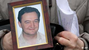 A woman holding a picture in her hands of the deceased Russian anti-corruption lawyer Sergei. (Photo: AP)