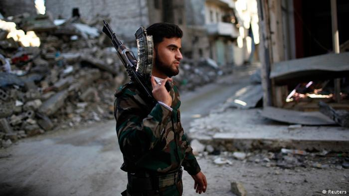 A Free Syrian Army fighter holds his gun as he walks to take up position at the front line during a fight with forces loyal to Syrian President Bashar al-Assad in Aleppo December 26, 2012. Photo: REUTERS/Ahmed Jadallah