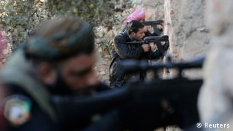 Free Syrian Army fighters aim their weapons during a gunfight with forces loyal to Syrian President Bashar al-Assad near Aleppo's airport December 26, 2012. REUTERS/Muzaffar Salman