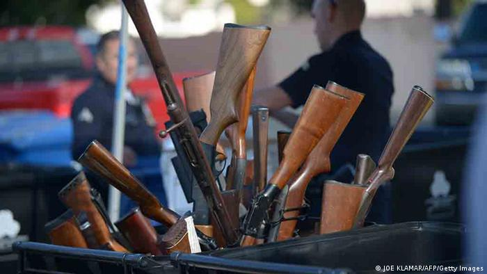 Rifles collected by LAPD Gun buyback program sticking out of trash bin