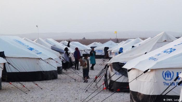 A half-dozen people walk amongst oblong tents in a desert setting (Copyright: Karen Leigh, DW)