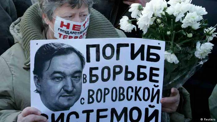 A woman holds a placard with a portrait of Sergei Magnitsky during a rally in Moscow in 2012. The poster reads 'Dead in the fight against the system of thievery'