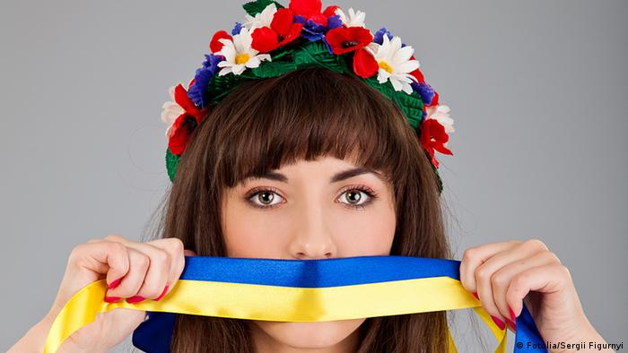 Cute Ukrainian woman with blue yellow band on the mouth isolated on a gray background. Sergii Figurnyi - Fotolia