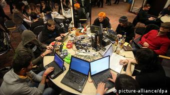 Several people sit in a circle and use laptops at a computer convention (c) Malte Christians/dpa