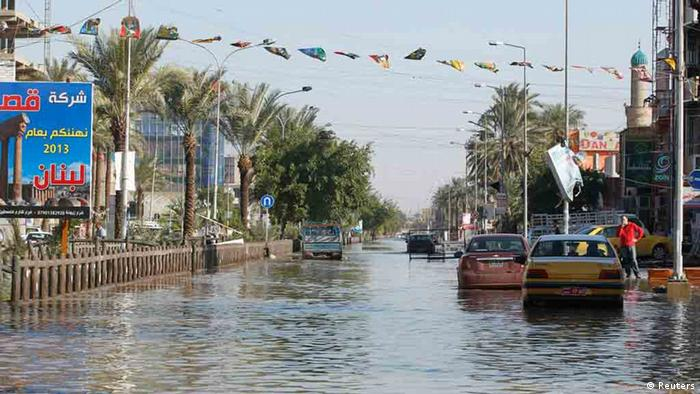 Cars are seen along a flooded street after overnight rain in Baghdad December 26, 2012. REUTERS/Saad Shalash (IRAQ - Tags - Tags: ENVIRONMENT DISASTER)