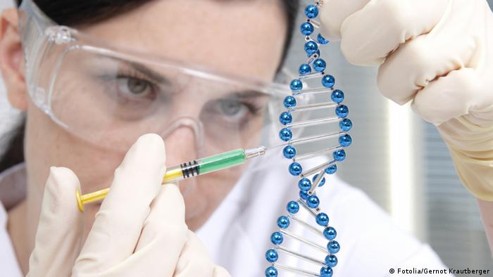 A woman examining a model of a DNA string