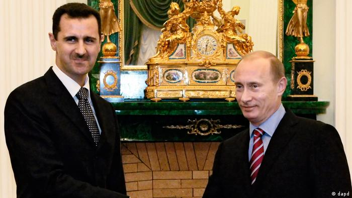 Syrian President Bashar Al-Assad stands next to Russian President Vladimir Putin, who's looking off-camera.