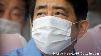 Japanese Prime Mister Shinzo Abe with a breathing mask on on a visit to Fukushima looks off camera with concern (Photo: ITSUO INOUYE/AFP/Getty Images)