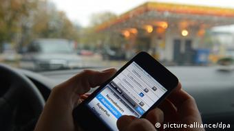 Мобильный телефон с приложением для сравнения цен на бензоколонках на фоне заправки