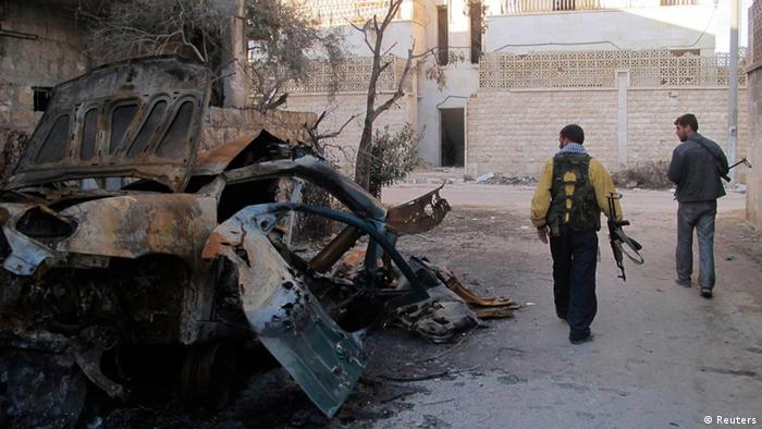 Free Syrian Army fighters walk past a burnt vehicle(Photo: Reuters)