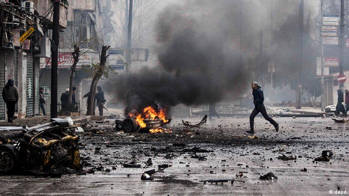 A man runs across a street littered with debris and the burning shell of a car (Photo:Narciso Contreras, File/AP/dapd)