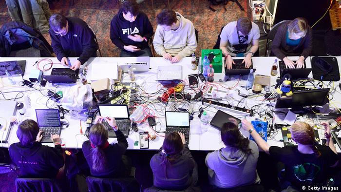 Chaos Computer Club-Mitglieder sitzen mit ihren Geräten am großen Tisch und diskutieren (Photo by Patrick Lux/Getty Images)