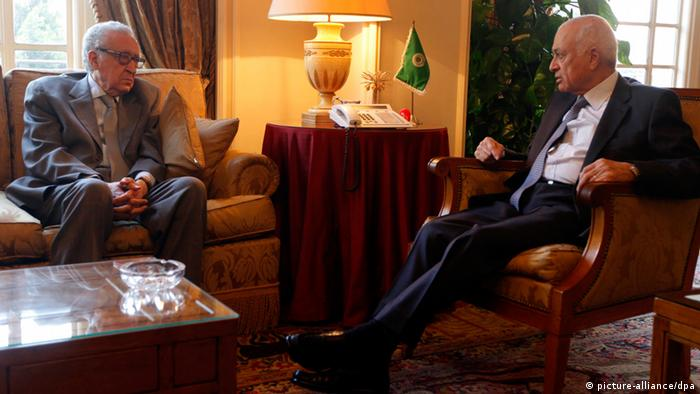 Two arabic men in business suits sit across from one another in a plush governmental office. (Photo: EPA/STR)