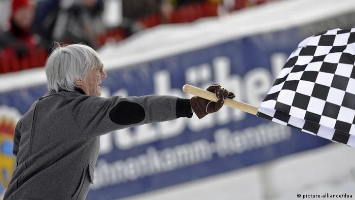 Formula One boss Bernie Ecclestone waves a chequered flag (photo via dpa)