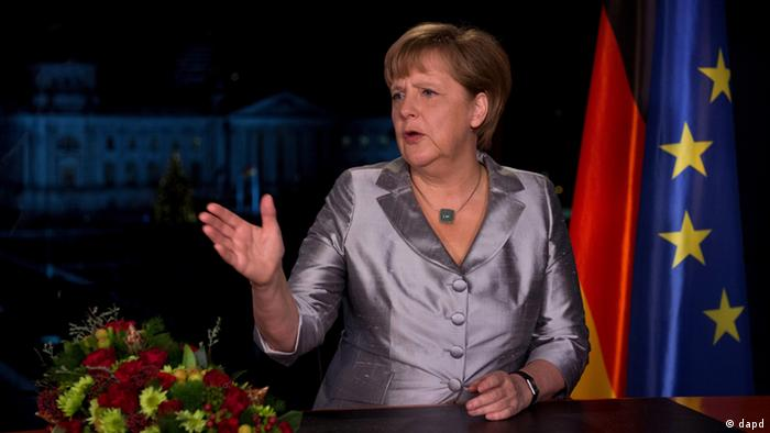 A still image from Merkel's address, she is gesturing towards her right in the picture.